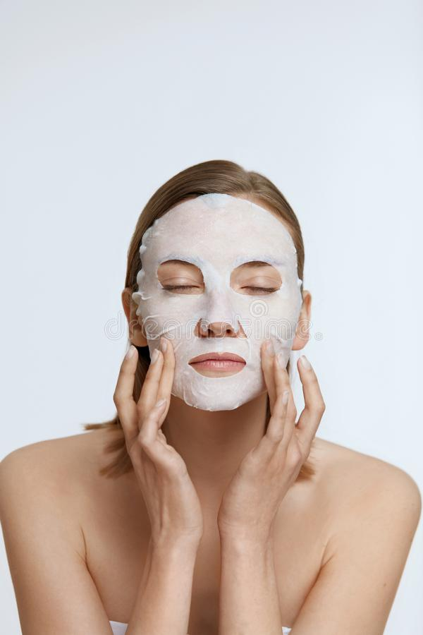 Free Facial Mask. Woman Using Sheet Mask On Face Skin For Spa Care Stock Photography - 157513922