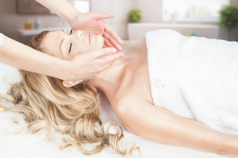 Facial massage. Beautiful young blond girl is having relaxing facial massage in the spa salon stock image
