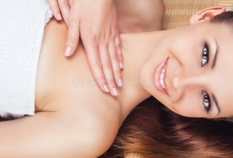 Facial massage. Beautiful young woman receiving facial and neck massage in a spa salon royalty free stock photos