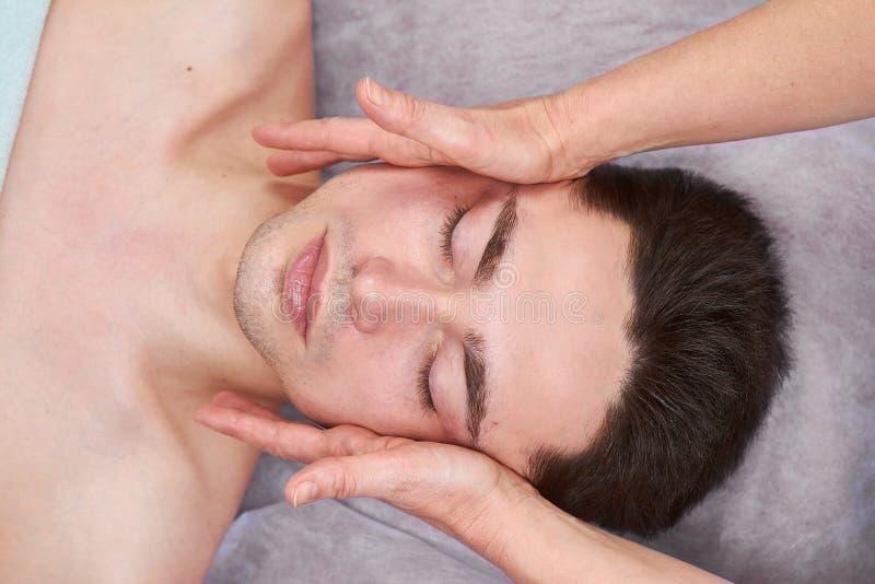 Facial massage, young handsome man. stock photos