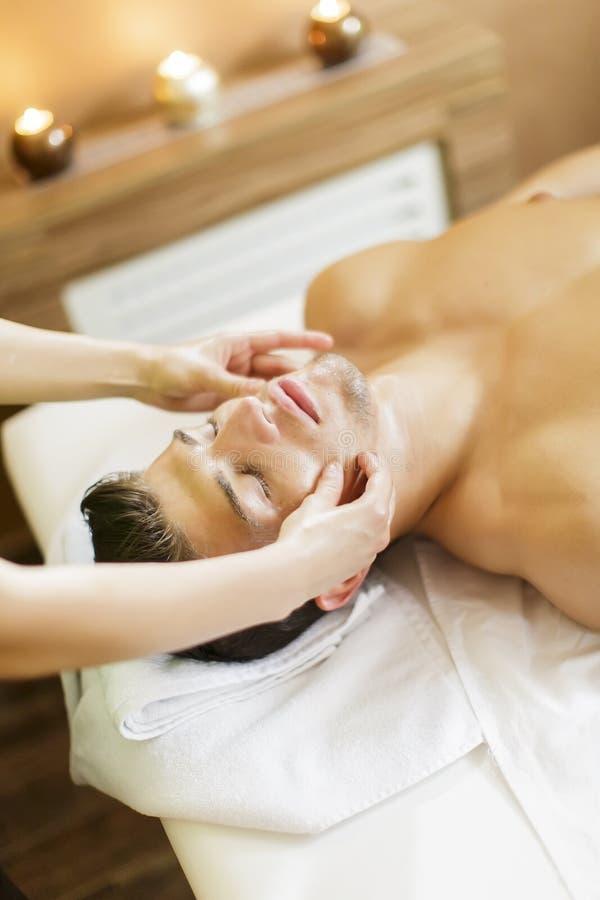 Facial massage. Young man having a facial massage stock images