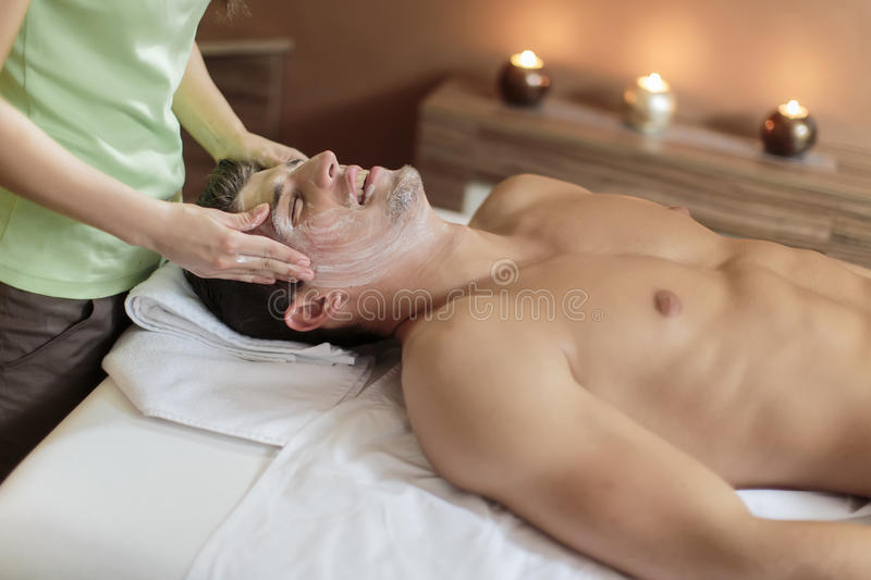 Facial massage. Young men having a facial massage royalty free stock images