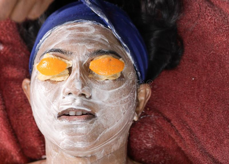 Facial pack mask applied on face of a lady with hair band with eyes closed with orange peel. herbal facial.  royalty free stock photo