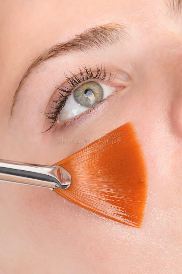 Facial peeling mask applying. Beauty salon, facial peeling mask with retinol and fruit acids stock photo