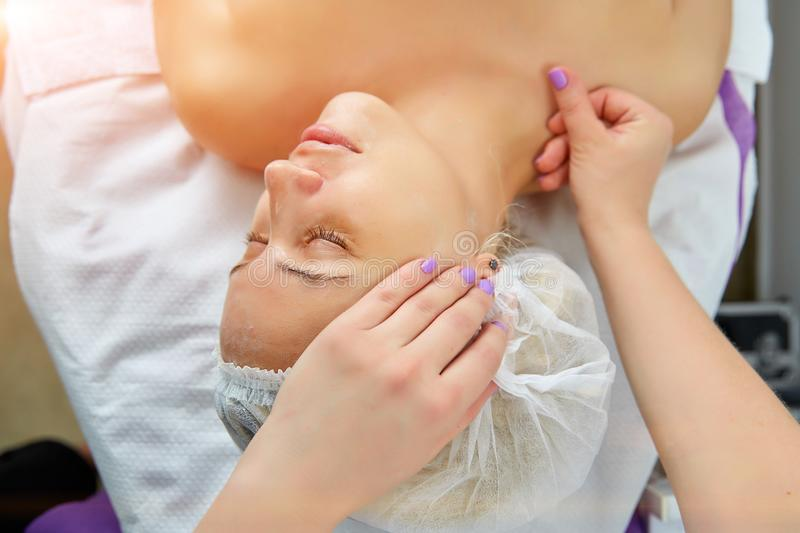 Young woman enjoying of facial massage in spa salon royalty free stock image