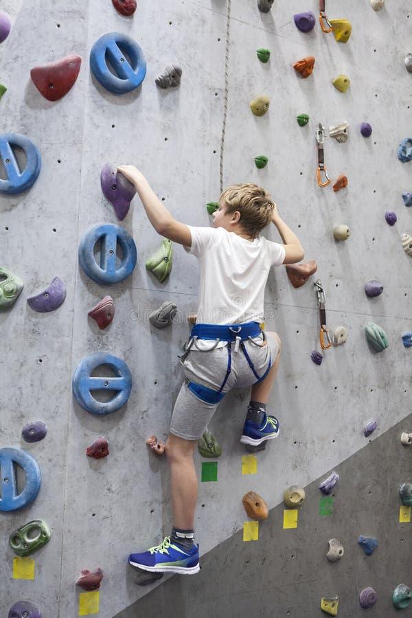 Facilidade de escalada artificial e menino caucasiano com linha da segurança na parede fotos de stock royalty free