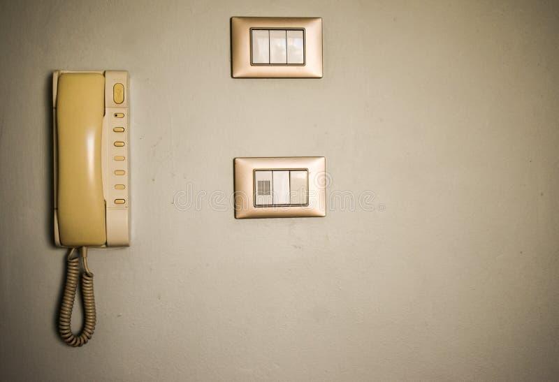 Facilità d'annata della camera di albergo Vecchi commutatori e telefono antico sulla parete bianca immagine stock libera da diritti
