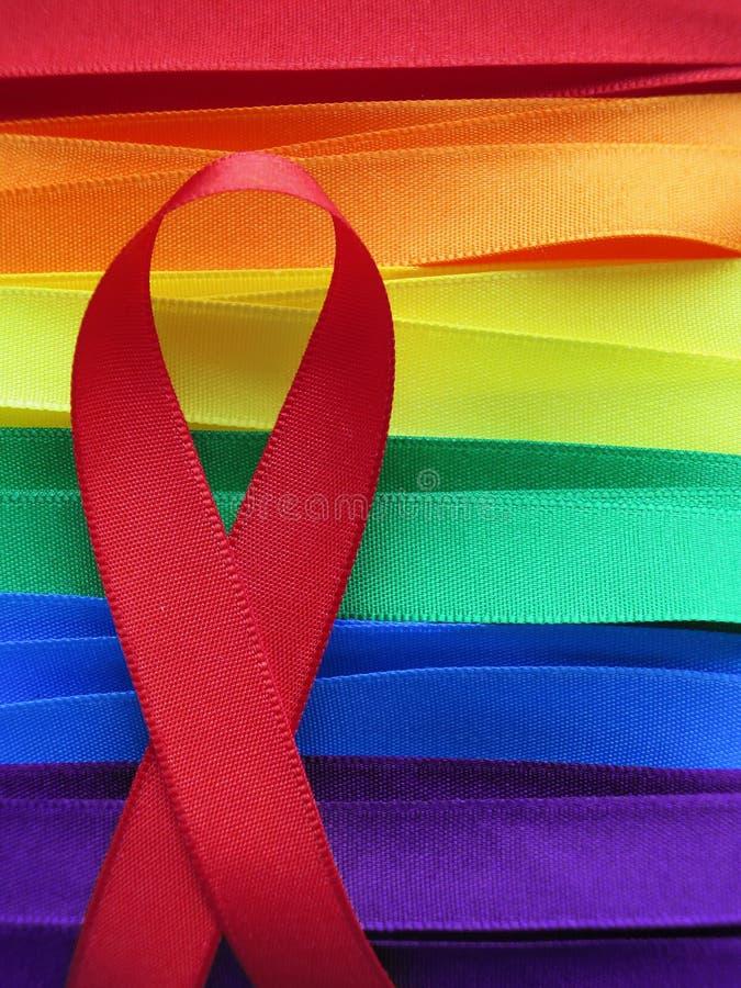 FACILITE le ruban rouge de conscience sur le drapeau gai coloré photographie stock