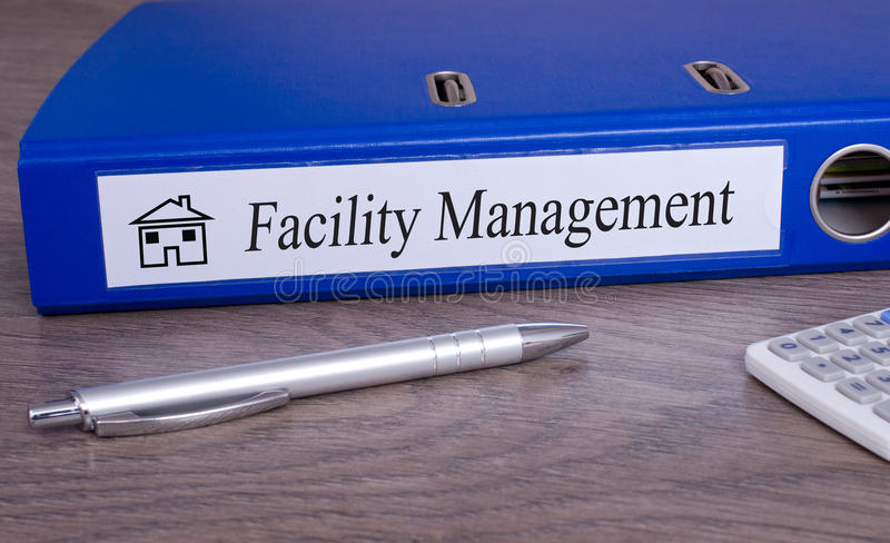 Facility Management. Binder on desk in the office with pen and calculator stock photography