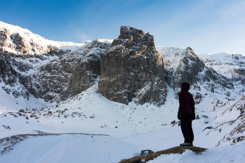 Young girl watching the beautiful frozen mountains during a sunny day of winter stock photography