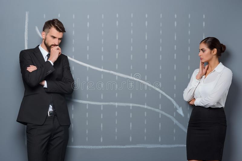 Facing a period of recession. A chart with arrows depicting downward trend. Two colleagues are in search of decision royalty free stock photos