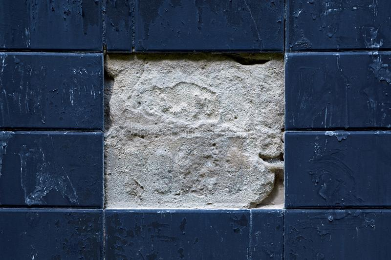 Facing plates on the wall of the building. Two Central tiles fell off royalty free stock photo