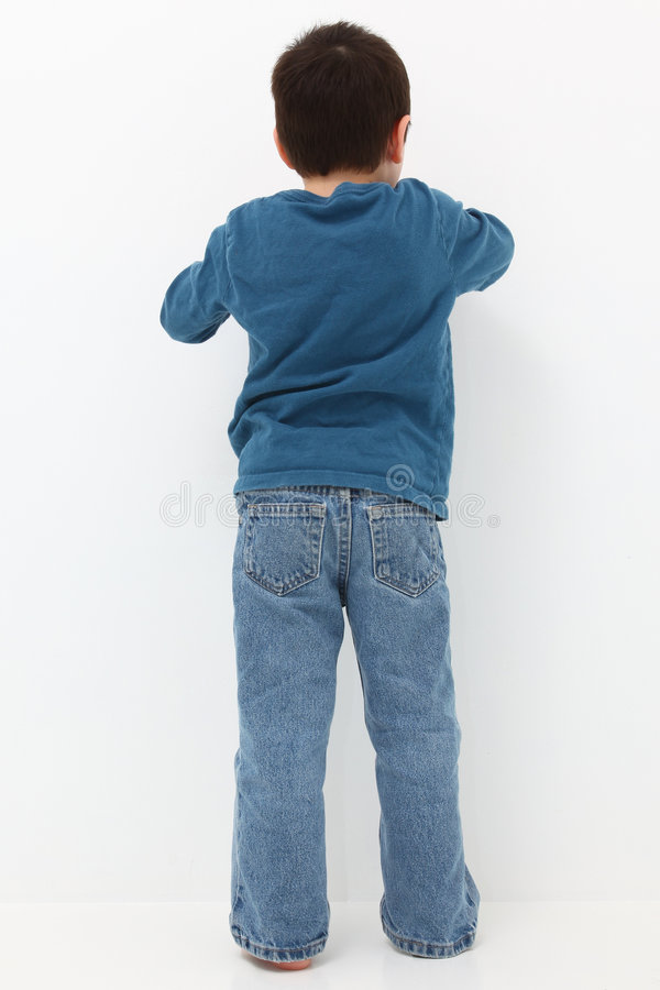 Facing Wall. Adorable five year old boy facing white wall stock image