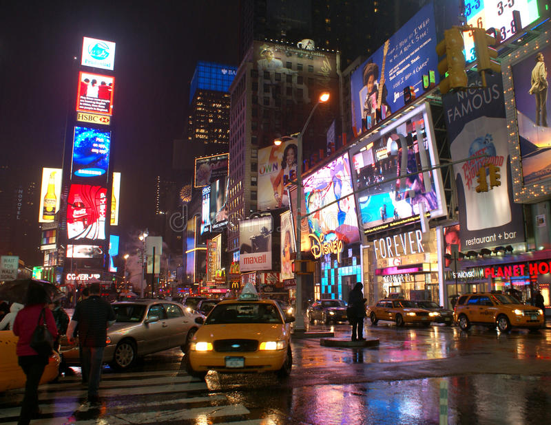 Facing a yellow cab, Times Square, New York City. Broadway avenue at the around Times Square in New York City, under the rain. Heavy traffic. Pedestrians are stock photography