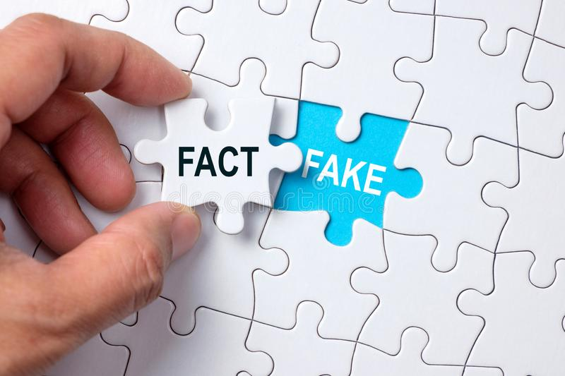 Fact and fake conceptual. Fake word on missing puzzle with a hand hold a piece of fact word puzzle royalty free stock photography