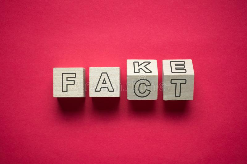 Fact and fake confusion. Confusion between fact and fake news using wooden cubes royalty free stock photos