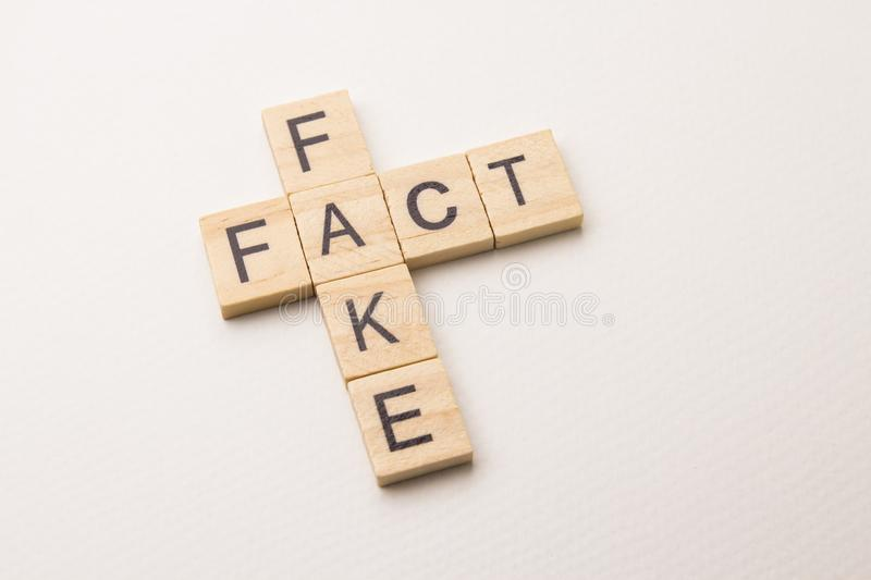 Fact&fake crossword on white background. Fact and fake - word phrase by letters block wood crossword on white paper background, in conception of news and royalty free stock photo