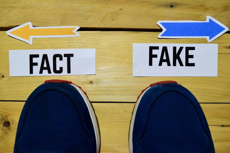 Fact or Fake opposite direction signs with sneakers on wooden. Vintage background. Business, education and finance concepts royalty free stock image