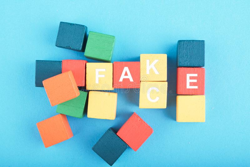 FACT OR FAKE word on colorful wooden cube. Over blue background stock photos