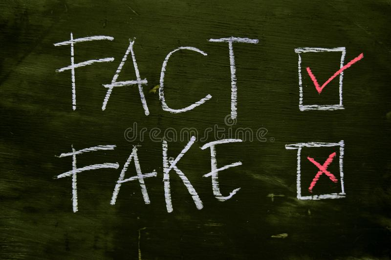 Fact or Fake written with color chalk concept on the blackboard royalty free stock photography