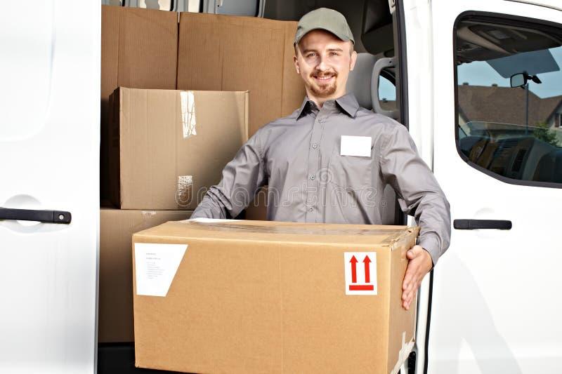 Facteur avec le colis près du camion de livraison photo stock