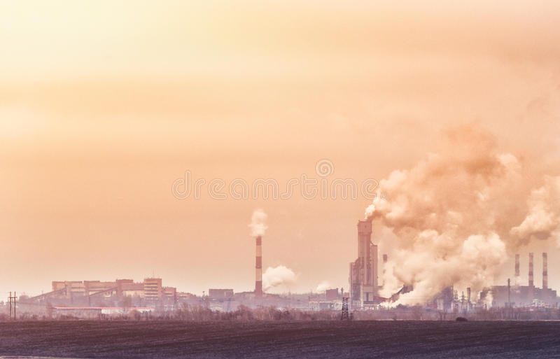 Factories with smoke from pipes dirty polluted industrial area in yellow and orange tones royalty free stock photos