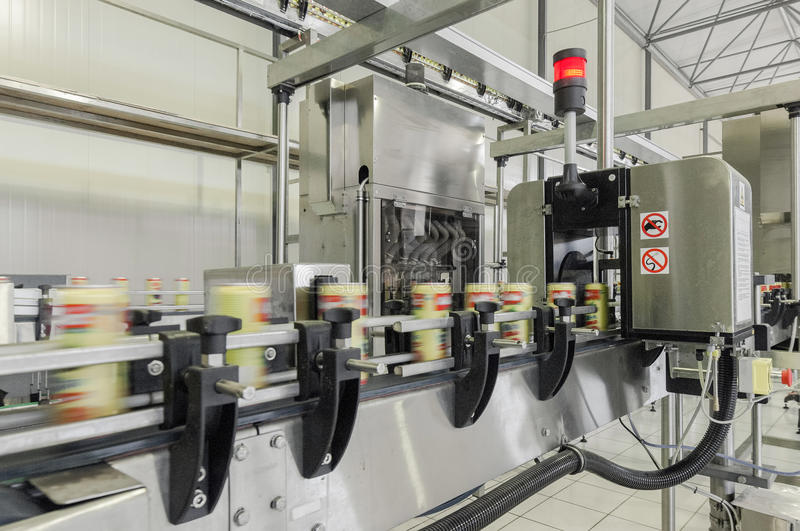 Factory for bottling beverages in cans. Close-up of conveyor belt in motion at production and bottling of drinks in tin cans. production and bottling of drinks royalty free stock images