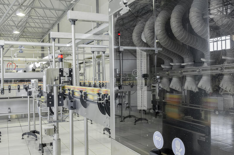 Factory for bottling beverages in cans. Conveyor belt in motion at production and bottling of drinks in tin cans. production and bottling of drinks in tin cans stock photo