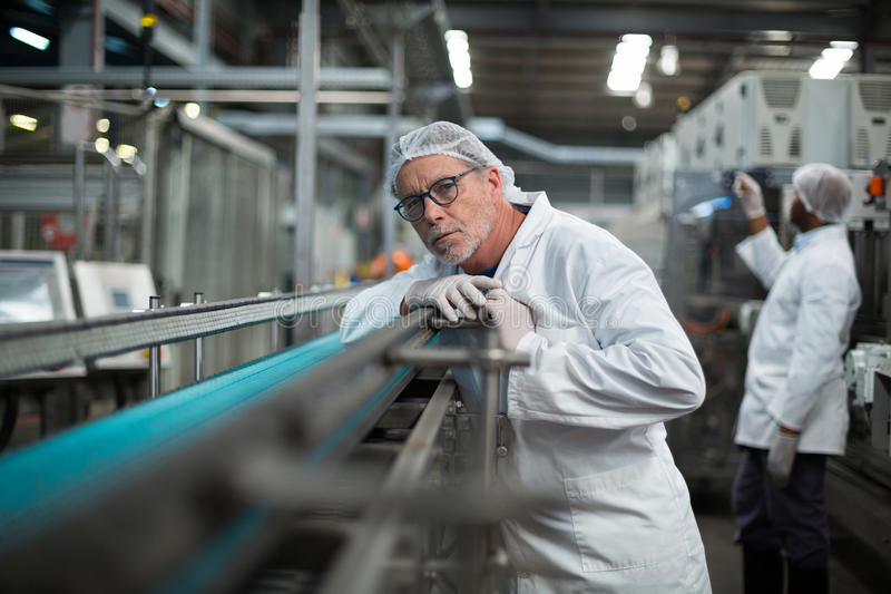 Factory engineer monitoring production line. In drinks production plant stock images