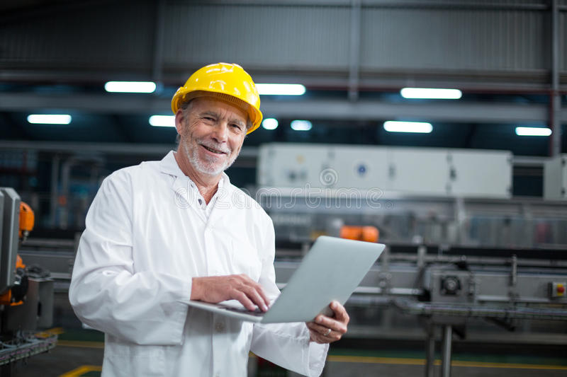 Factory engineer using laptop in the factory. Portrait of factory engineer using laptop in drinks production plant stock images