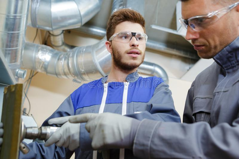 Factory engineers operating hydraulic tube bender royalty free stock photo