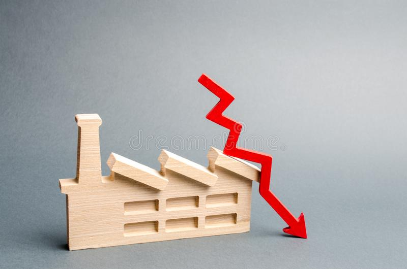 Factory figurine and red down arrow. The concept of a fall in the level of production and the level of the economy. Industry. Recession, unprofitability of stock photography