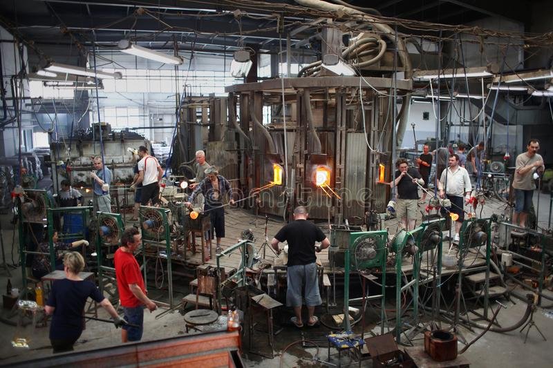 Back-looking technology of glass production. Factory floor in glassworks. Teamwork during traditional handmade glass production stock photo