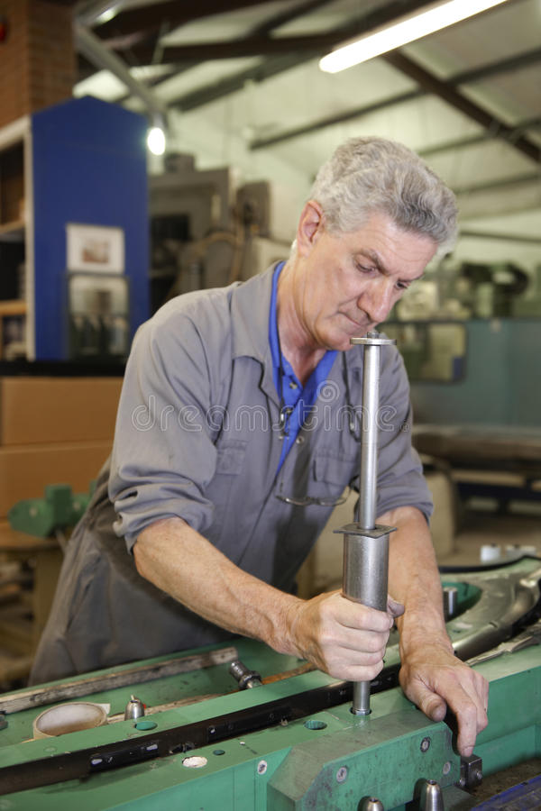 Factory floor worker. Senior worker on factory floor in the manufacturing industry stock photography