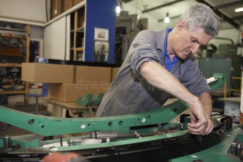 Factory floor worker. Senior worker on factory floor in the manufacturing industry stock photos
