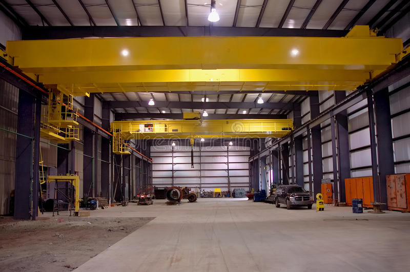 Factory Interiors. A view of a new large factory having interiors installed with overhead cranes royalty free stock image