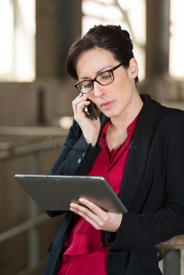 Factory marketing supervisor looking at information on tablet stock photography