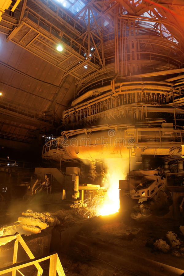 Factory with molten metal. Factory interior lit with the glow of molten metal stock images