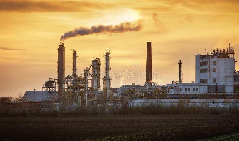 Factory pipe polluting air, smoke from chimneys against sun, environmental problems, ecological theme, industry scene royalty free stock images