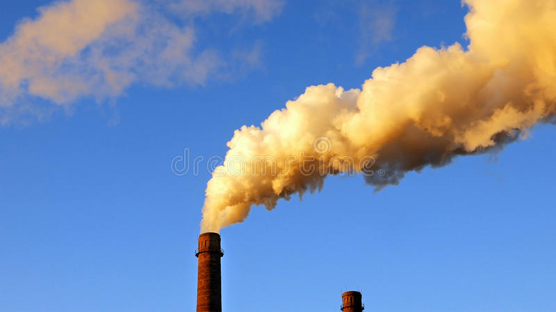 Factory plant smoke stack over blue sky background. Energy generation and air environment pollution industrial scene stock images
