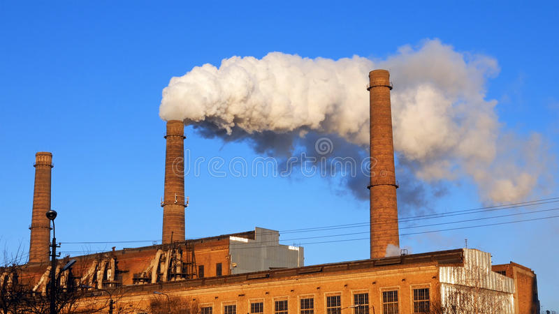 Factory plant smoke stack over blue sky background. Factory plant puffs smoke stack over blue sky background. Energy generation and air environment pollution stock image