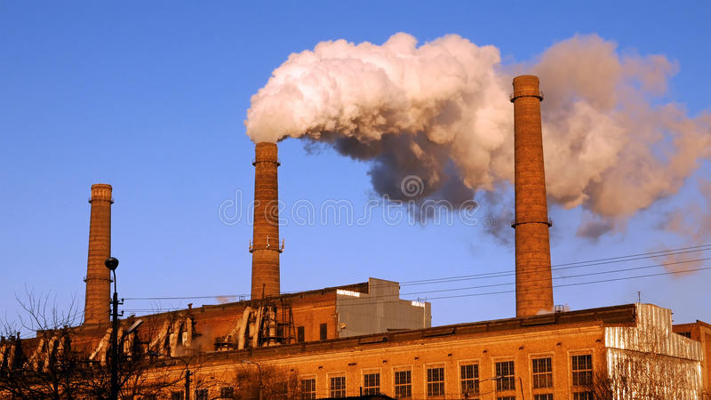 Factory plant smoke stack over blue sky background. Factory plant puffs smoke stack over blue sky background. Energy generation and air environment pollution royalty free stock images