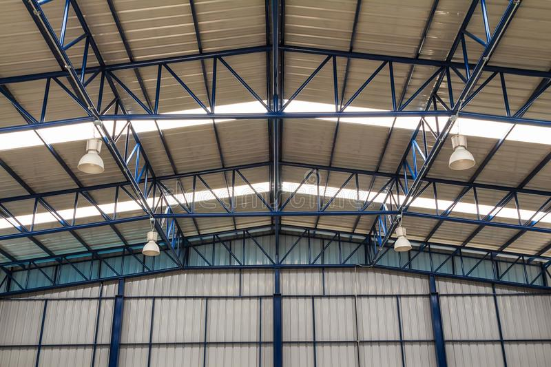 Factory roof and truss. With industrial overhead lighting fixture hanging on the truss royalty free stock photos