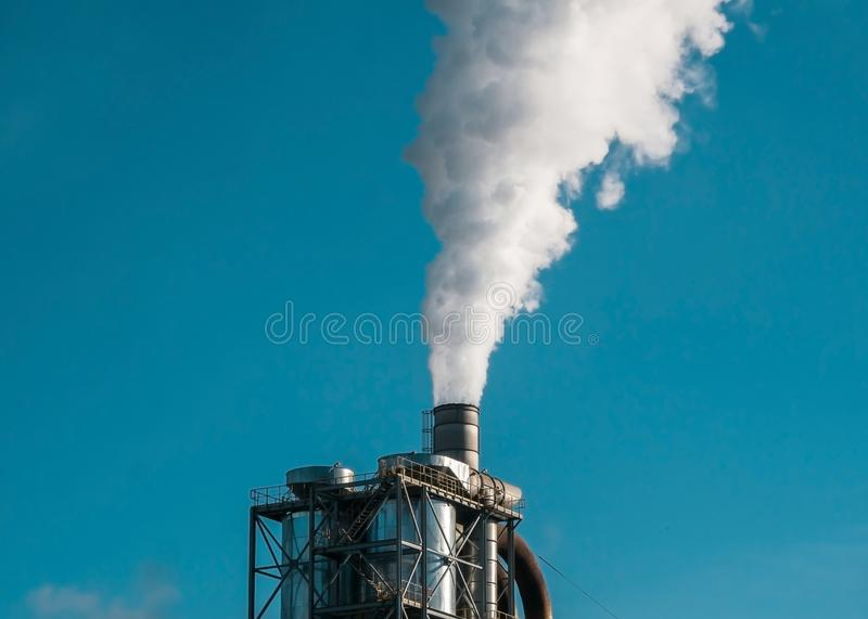 Factory smog ejecting pipes into the environment stock images