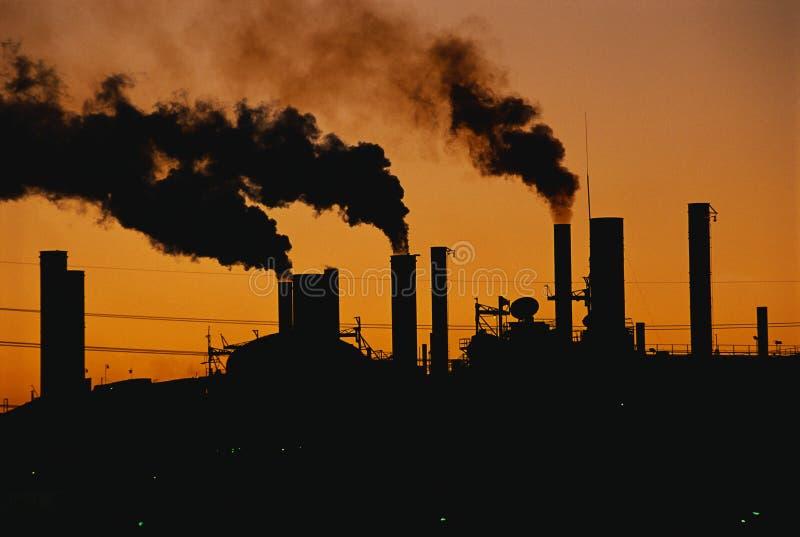 Factory with smokestacks at sunset stock photo