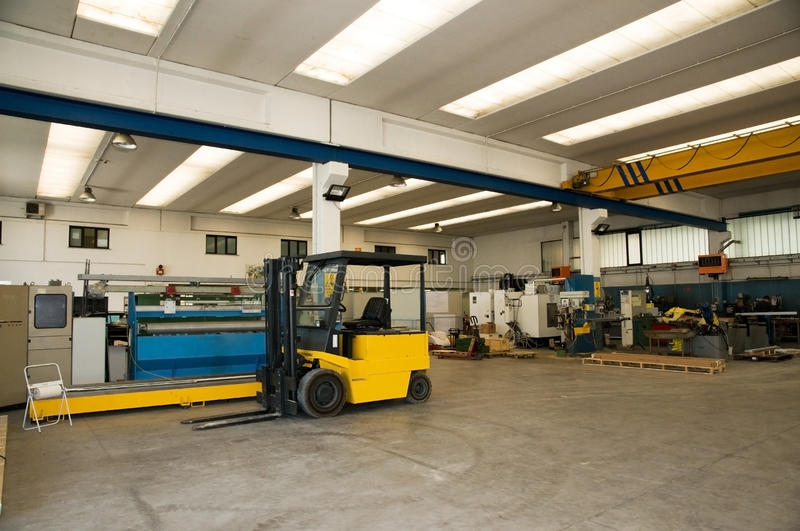 Factory warehouse with forklift. Inside of factory warehouse with forklift and goods stock images