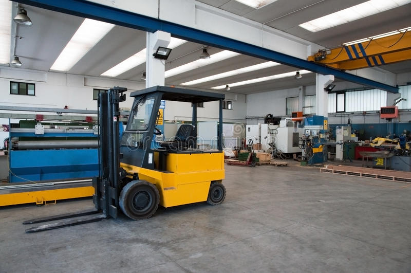 Factory warehouse with forklift. Inside of factory warehouse with forklift and goods stock image
