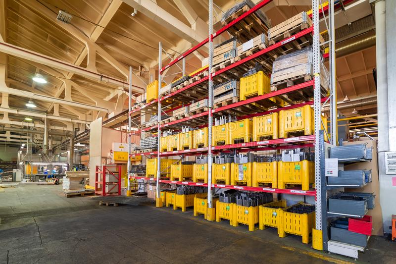 Factory warehouse steel reinforcement. large yellow plastic boxes on the shelves. Industrial distribution warehouse royalty free stock image