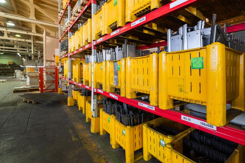 Factory warehouse steel reinforcement. large yellow plastic boxes on the shelves. Industrial distribution warehouse stock photos