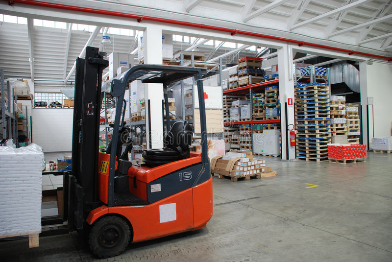 Factory wharehouse with forklift. Inside of factory wharehouse with forklift and goods royalty free stock photography